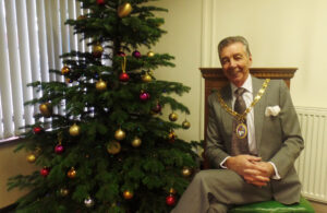 Photo of Mayor Cllr Holbrook sitting next to the Christmas tree at the Town Council offices