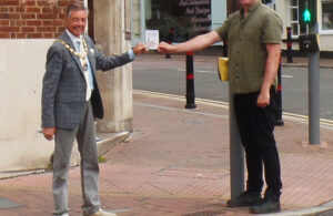 Photo of Mayor Cllr Paul Holbrook and Chris Beveridge in town centre holding a Hailsham Card