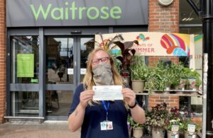 Photo of youth worker Kieran Baker holding Waitrose Community Matters donation cheque