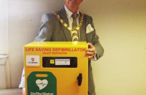 Photo of Mayor Cllr Paul Holbrook holding defibrillator equipment donated by Haulaway Ltd